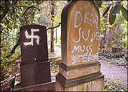 June 27, 2004. Grave Desecration. A Jewish gravestone in Dusseldorf, Germany, is pictured on Friday, after more than 40 desecrated graves were discovered at the Jewish cemetery. Nazi and SS symbols were also sprayed in silver paint nearby. Police said they did not know yet who was responsible for the vandalism. Photo: AP.
